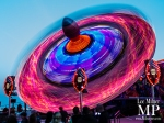 neon-lit fiarground ride, looking like an enormous blue and pink spinning top.