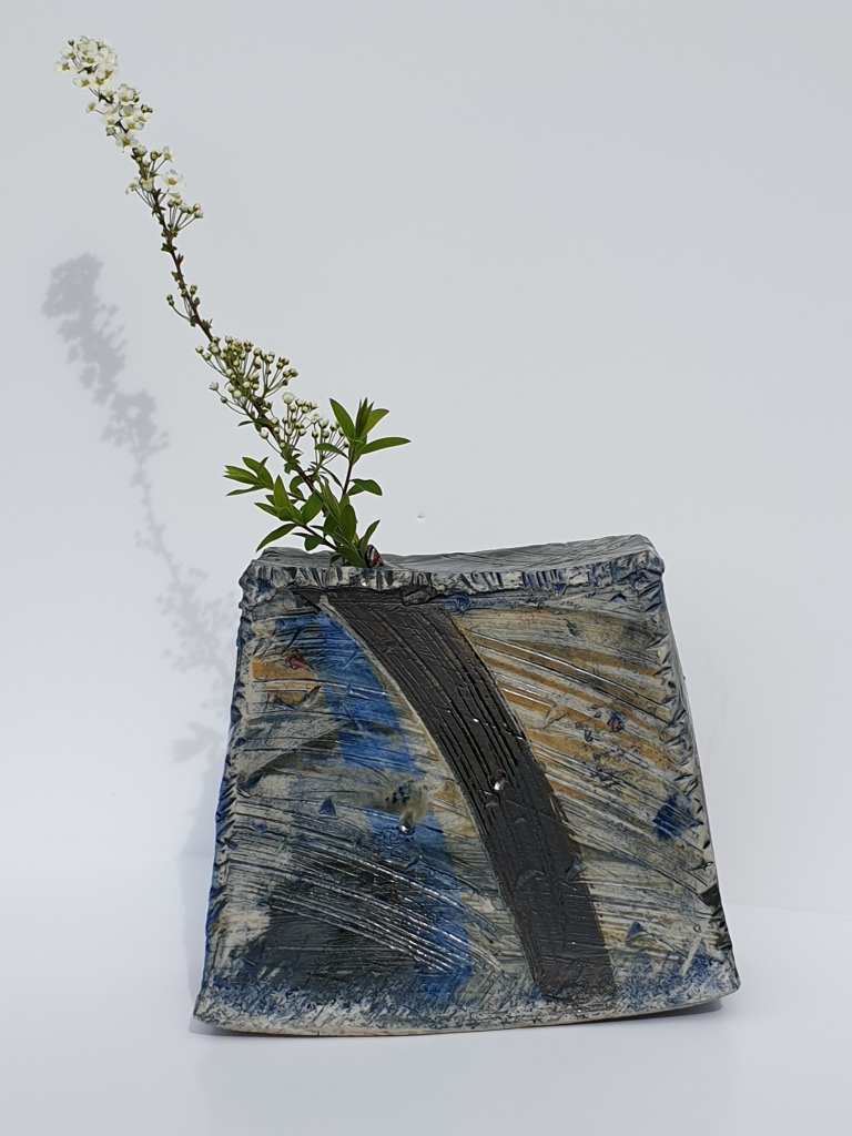 Rough, flattened rectangular vase in muted grey, dark blue, brown. It almost looks like a ploughed field, with rough grass at the edges and lines running across. The artist is inspired by aerial photos of rural landscape, so this is intentional.